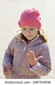 little girl  looking at the ladybug on her hand