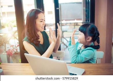Little girl looking at laptop computer with her mom.Concept family happy.