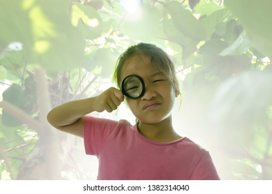 Little girl looking with magnifying glass