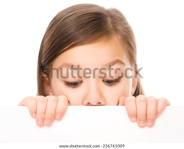 Little girl is looking from out blank board, isolated over white