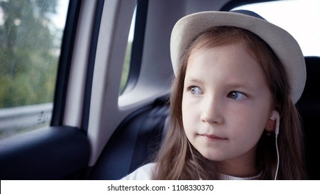 Little girl looking out from car window at sunny day