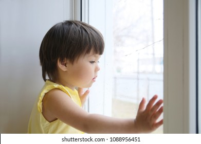 little girl looking out the window longing for some sunshine. curiosity childness. child sitting home at rainy day