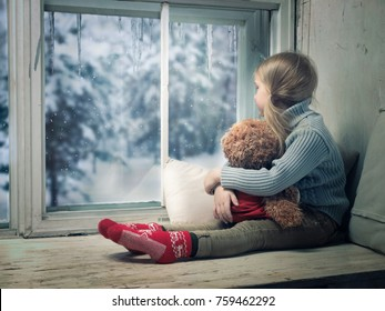 Little girl looking out the window. Outside, the winter snow. A wide window sill. A child hugs a plush bear