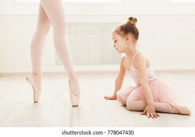 Little girl looking at professional ballet dancer. Cute baby dreaming to become ballerina, copy space. Classical dance school background, practicing for children, crop