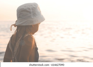 Little Girl Looking At The Sea At Sunset