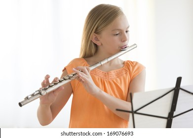 Little girl looking at sheet music while practicing flute at home