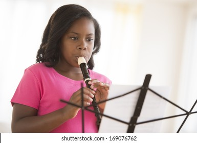 Little girl looking at sheet music while playing flute at home