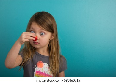 Little girl looking at a strawberry