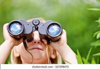 Little girl looking through binoculars outdoors