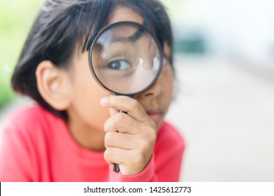 little girl looking through a magnifying glass on nature park.Eye care,Eye clinic and Education, Investigator concept.
