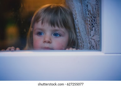Little girl looking through window.