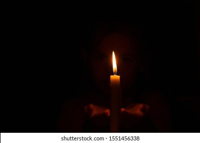 little girl looks at a burning candle in absolute darkness