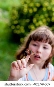 Little girl looks at a butterfly. Aglais urticae L.
