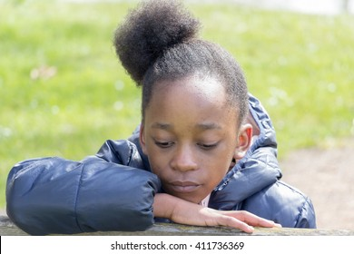 Little girl looks down with sad expression