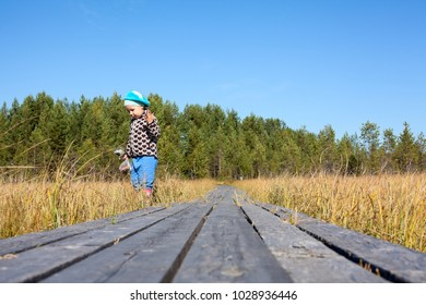 Little girl looks for in grass standing near wooden planks of pathway passing through the swampland, copyspace