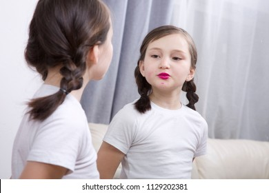 A little girl looks in the mirror and paints her lips with bright lipstick.