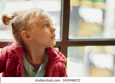A little girl looks to the side by the window