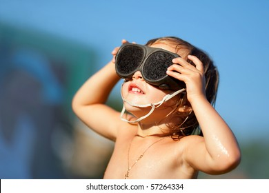 Little girl looks at sun on summer day with glasses