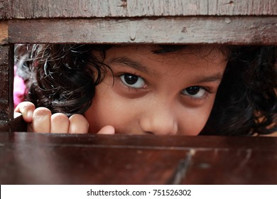 Little girl looks through the gap in a wooden chair.