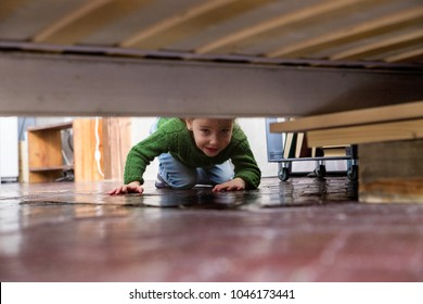 little girl looks under the bed