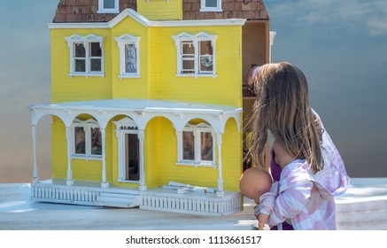 a little girl is lost in wonder as she examines this beautiful old vintage doll house