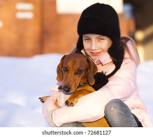 little girl and a loving puppy dachshund