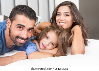 Little girl lying in bed with her parents