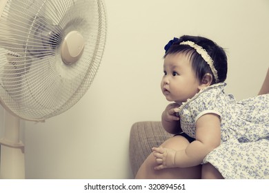 The little girl was lying exposed electric fans because the heat, process color.