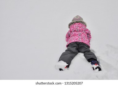 Little girl lying facing down the snow