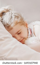little girl  lying with her eyes closed. child sleeps with  favorite toy Lying soft pillow under warm blanket. dream serene. Waking up.  early morning  bright sunlight.