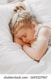little girl  lying with her eyes closed. child sleeps with  favorite toy Lying soft pillow under warm blanket. dream serene. Waking up.  early morning  bright sunlight