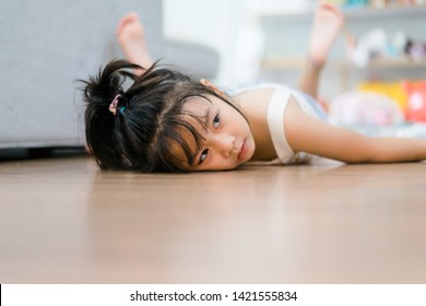 Little girl lying and lazy moment on laminate floor.Child girl tired and low battery want to sleep at home.