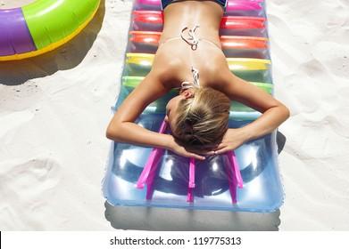 Little girl lying on air mattress on sandy beach and enjoys in sunbathing