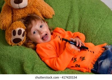 little girl lying on a big green pillow