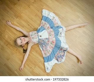 Little girl lying on the floor with legs and hands apart.