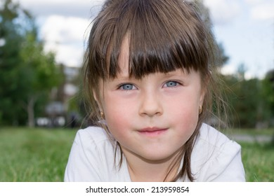 little girl lying on the grass in the park, facing the camera