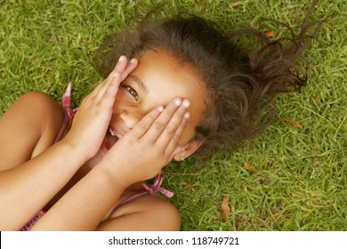 Little girl lying on the green grass on her back playing peek a boo with the camera peering out between her fingers which are covering her face