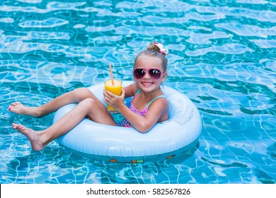 Little girl lying on inflatable ring in swimming pool. In the hands of a glass of mango juice. Holidays.