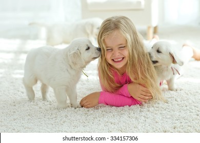 Little girl lying on the mat with labrador, smiling at camera at home in the living room
