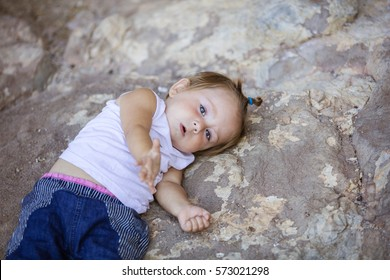 Little girl lying on rock and stretching out hand. Playful mood or asking for help concept.