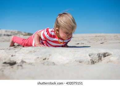 Little girl lying on the sand and watching insects.Concept for nature, discovery, exploring