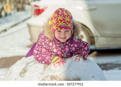 Little girl lying on the snow. Child in a pink warm hat and jacket lying on the stone street and smiling. On the stone is the snow behind the car. Autumn in Russia