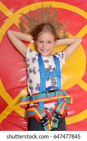 Little girl lying on trampoline in entertainment center.