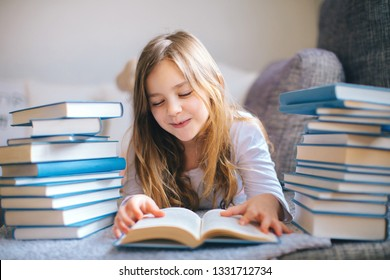 Little girl lying and reading book