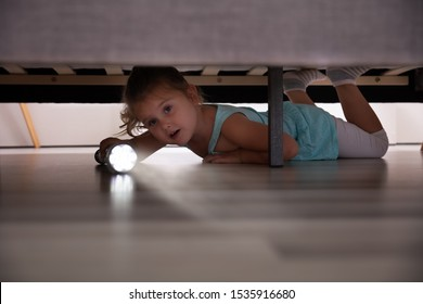 Little Girl Lying Under The Bed Searching For Something With Flash Light At Home