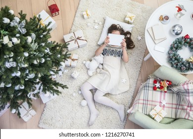 Little girl is lying under the Christmas tree with a tablet on the carpet. View from above