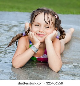 Little girl lying in the water stream on child splash pad playground. Summer fun while getting wet and refresh.