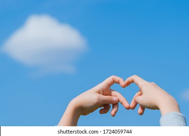 Little girl made a heart with her fingers against the blue sky.love Concept, Heart-shape hand gesture.