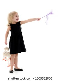 A little girl with a magic wand. Concept of happy childhood, holiday, Christmas and birthday. Isolated over white background