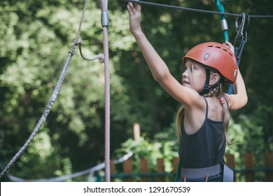 little girl make climbing in the adventure park. Concept of sport life.